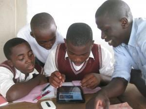 Students at the Tassah Academy (Cameroon AFRICA) use a donated tablet computer to connect their classroom with a classroom in California (USA)